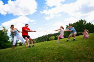 parents and children playing tug-of-war on summer day