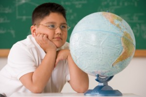 middle school boy looking at a globe